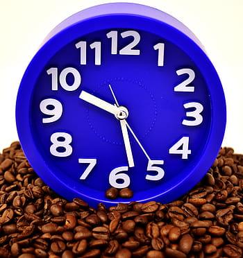 Imagen de un reloj sobre granos de café. Coffee Break.